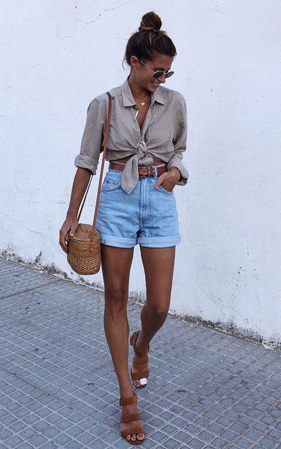 Chica con shorts denim y camisa anudada al frente.