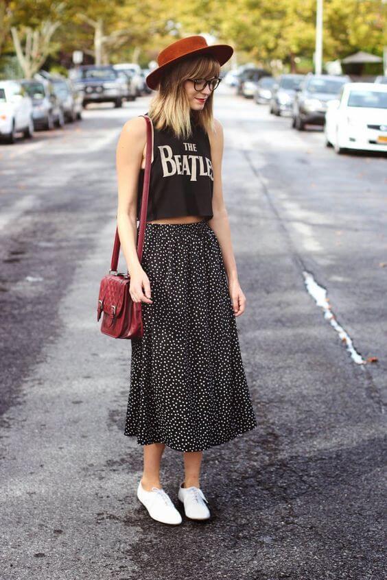 Chica con falda de topos, camiseta negra, sombrero y bolso.
