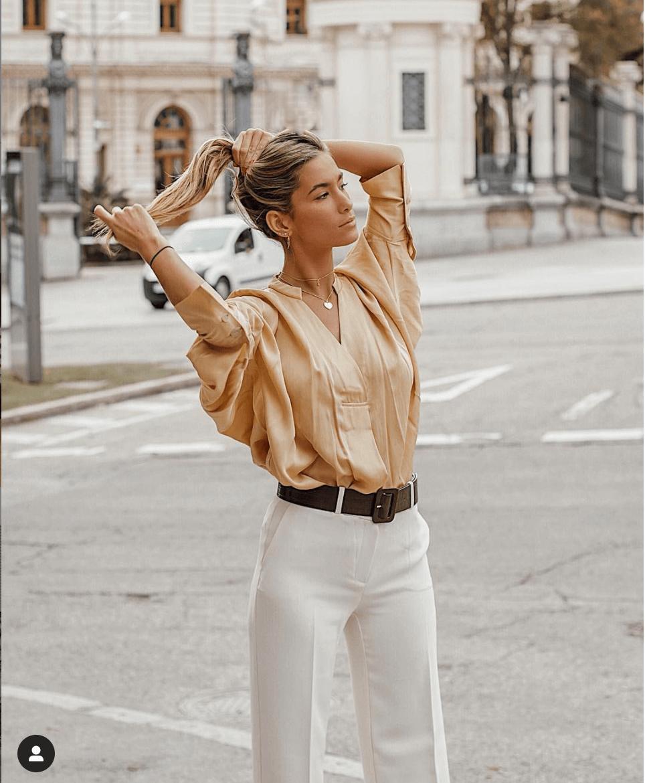 La influencer con un look de pantalón blanco y blusa dorada