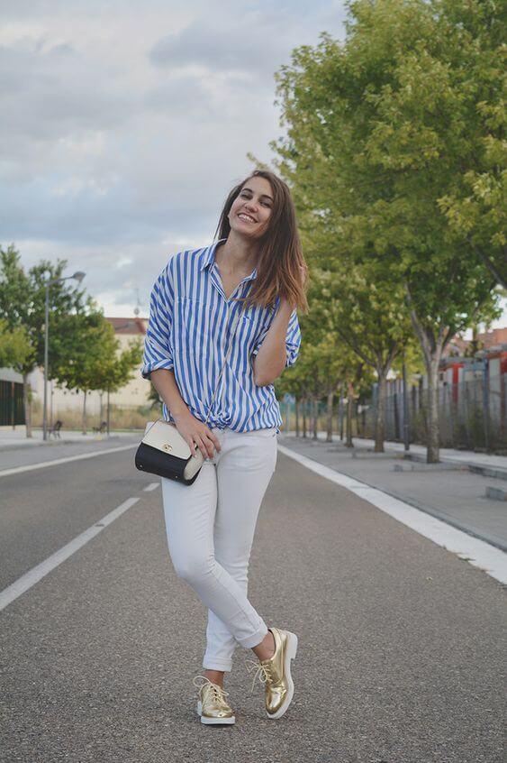 Chica con pantalón blanco y camisa a rayas.
