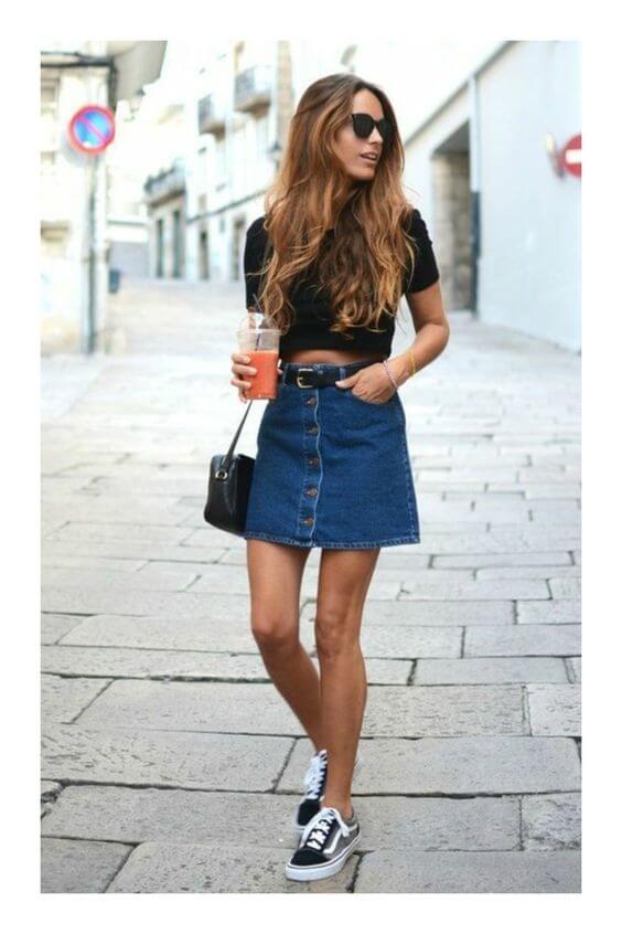 Chica con minifalda en A vaquera y camiseta negra.