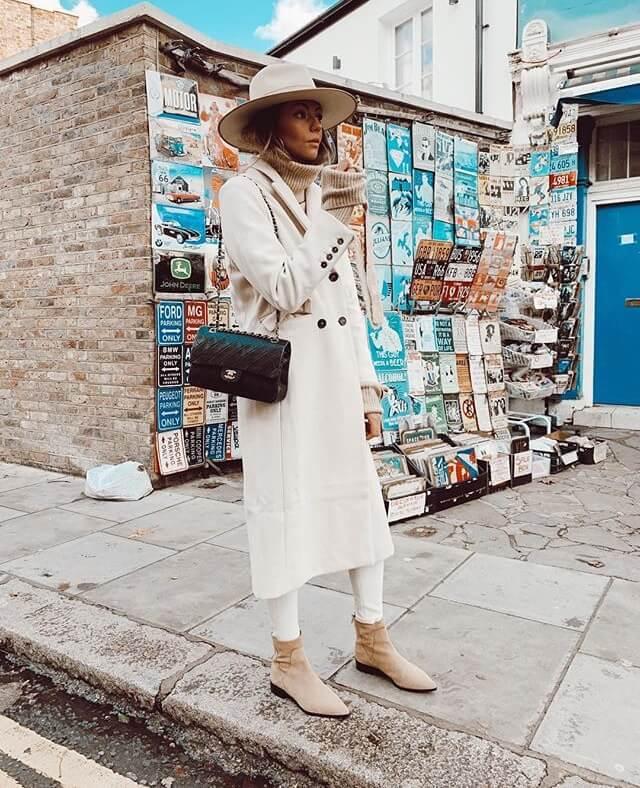 Influencer Aretha Fusté con abrigo largo blanco.