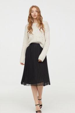 Falda acordeón en color negro a media pierna de H&M.