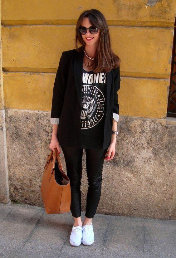 Look de vaqueros negros, camiseta estampada, blazer negro y zapatillas blancas.