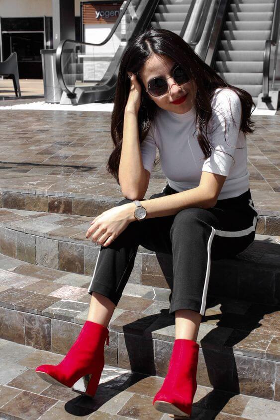Outfit blanco y negro con botines con tacón en rojo.