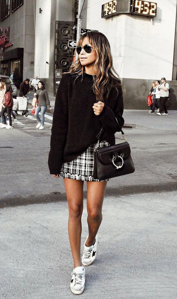 Look casual de jersey negro con falda corta.