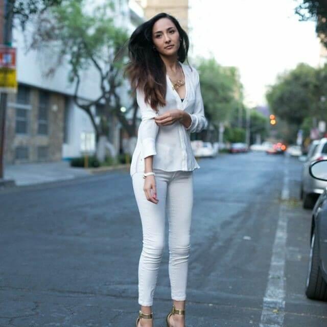 Outfit de blusa y pantalón blanco con accesorios dorados.