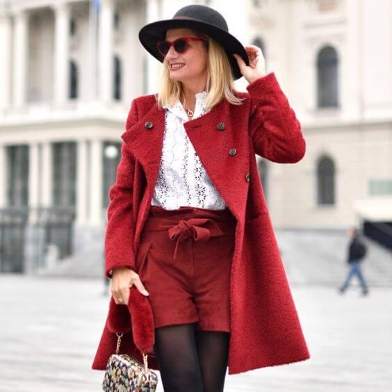 Chica con pantalones cortos y saco en color rojo.