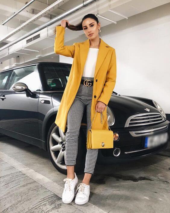 Chica con pantalones de cuadros en blanco y negro y saco color amarillo.
