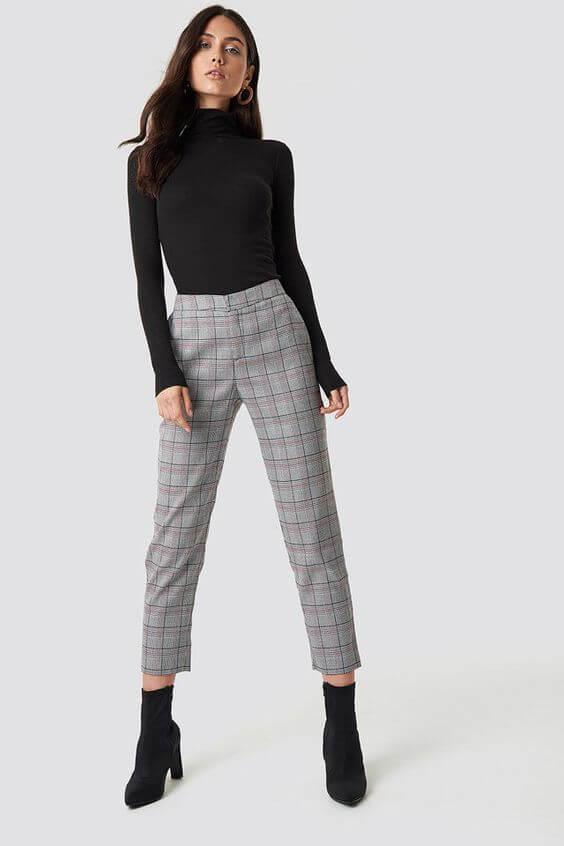 Chica con pantalones de cuadros en color gris y jersey negro.