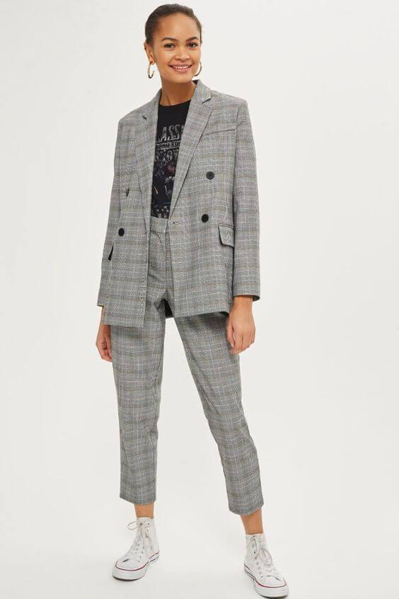 Look de traje gris con estampado de cuadros.