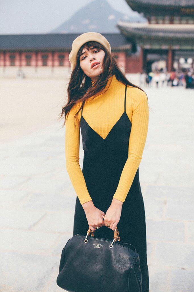 Combinación de vestido negro sobre un jersey amarillo canario.