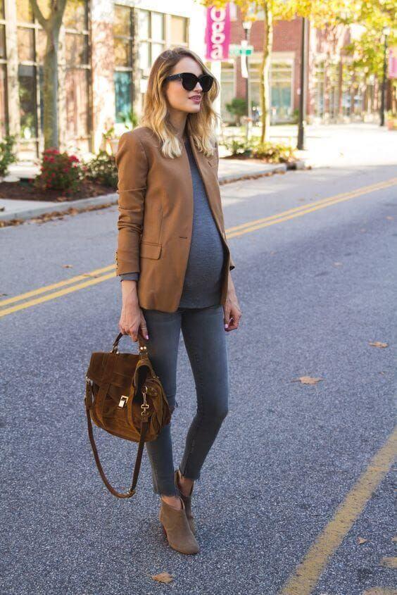 Chica embarazada con jeans, bolso y americana marrón.