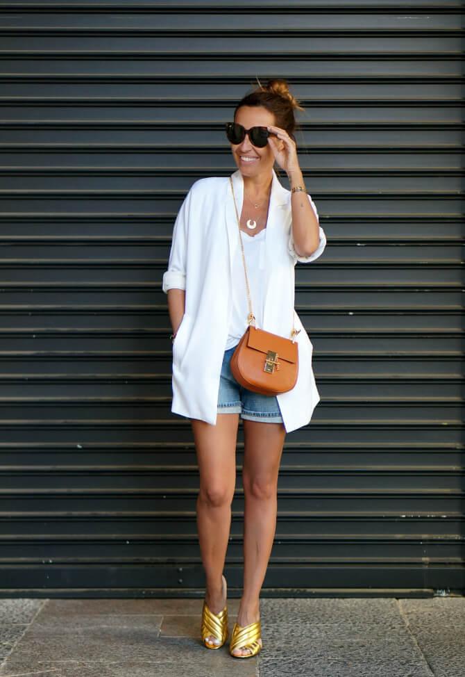 Look de blazer blanca con shorts vaqueros.