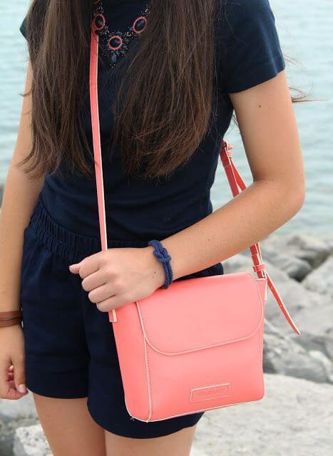 Chica luciendo bolso bandolera en color living coral.