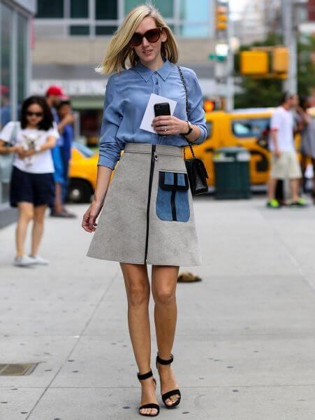 chica en la calle con camisa azul y falda gris en evasé