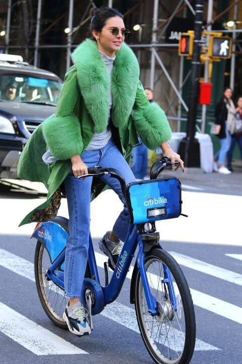 kendall jenner en bicicleta con abrigo de pelo verde y jeans