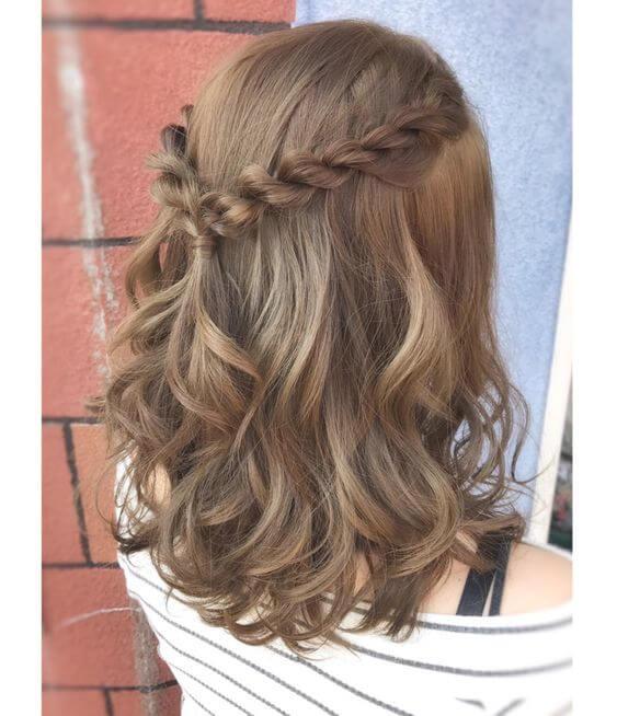 Chica con el cabello corto con un semirecogido de trenzas.