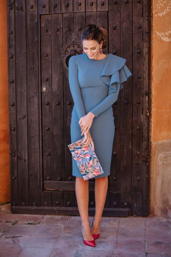 Look para ser la invitada perfecta: vestido gris de manga larga y clutch.