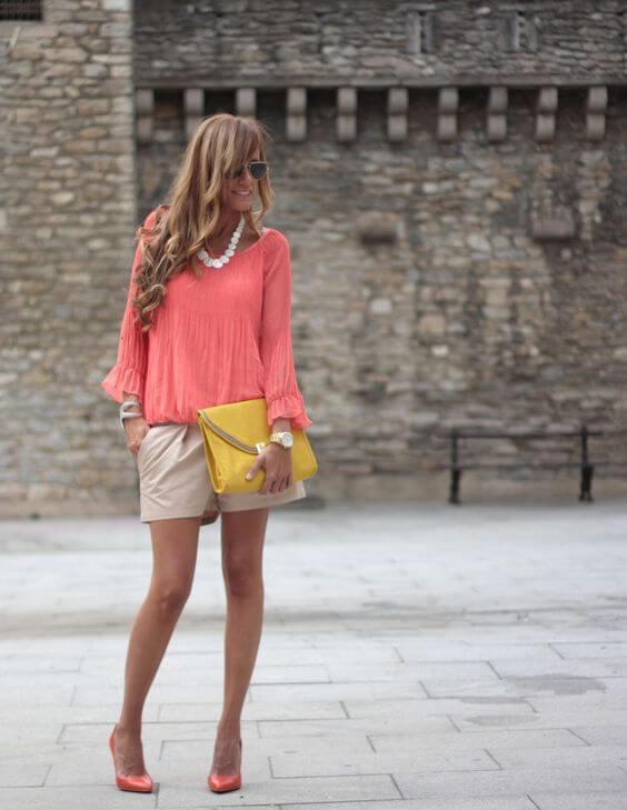 Chica con short beige y blusa living coral con clutch mostaza.