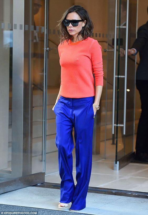 Victoria Beckham con pantalón azul y jersey living coral.